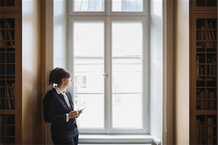 Female professional listening music while looking through window at library Stock Photo - Premium Royalty-Free, Code: 698-08580347