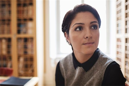 Close-up of female lawyer looking away in library Stock Photo - Premium Royalty-Free, Code: 698-08580355