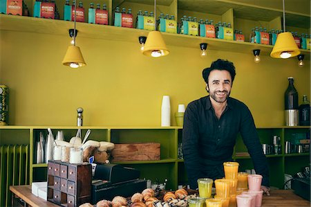 Portrait of smiling male owner standing in coffee shop Stock Photo - Premium Royalty-Free, Code: 698-08685417