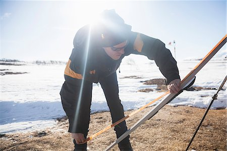 Mature man in warm clothing applying grip tape on ski at snow covered landscape Stock Photo - Premium Royalty-Free, Code: 698-08685478
