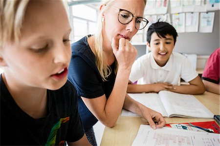 Teacher and students reading from book in classroom Stock Photo - Premium Royalty-Free, Code: 698-08784033