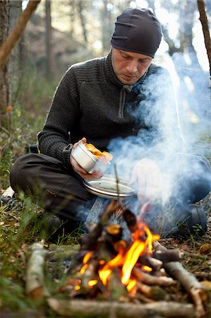 front - Man cooking chanterelle mushrooms at bonfire in forest Stock Photo - Premium Royalty-Free, Code: 698-08783903