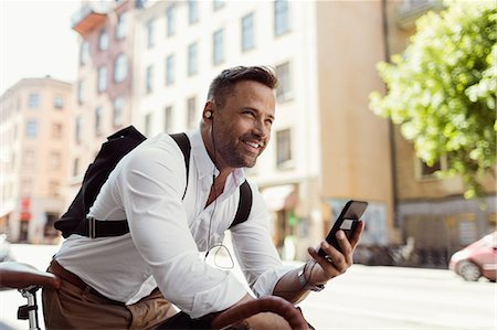 Smiling businessman looking away while holding smart phone on street Stock Photo - Premium Royalty-Free, Code: 698-08803599