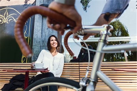 Cropped image of businessman with bicycle talking to colleague at sidewalk cafe Stock Photo - Premium Royalty-Free, Code: 698-08803630
