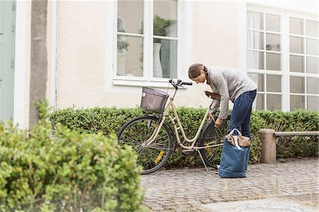 Woman locking bicycle by plants outside house Stock Photo - Premium Royalty-Free, Code: 698-08803689