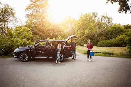 Family by black electric car against trees at park Stock Photo - Premium Royalty-Free, Code: 698-08841512