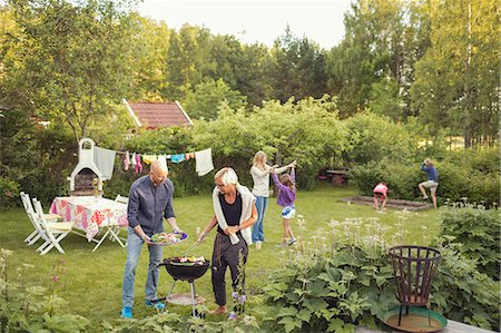 Man and woman cooking vegetables on barbecue grill with kids enjoying garden party Stock Photo - Premium Royalty-Free, Code: 698-08885805