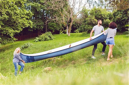 Friends carrying canoe on grassy field by trees Stock Photo - Premium Royalty-Free, Code: 698-08886079