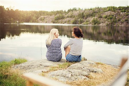 Rear view of female friends talking while sitting at lakeshore Stock Photo - Premium Royalty-Free, Code: 698-08886072