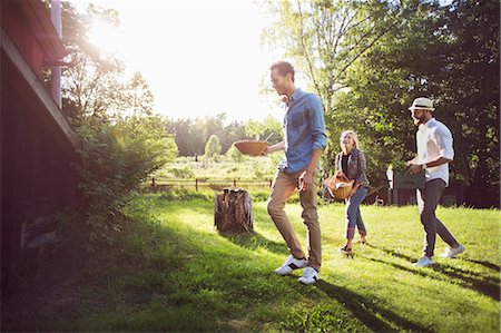 Happy friends holding crate and containers while walking on grassy field Stock Photo - Premium Royalty-Free, Code: 698-08886117