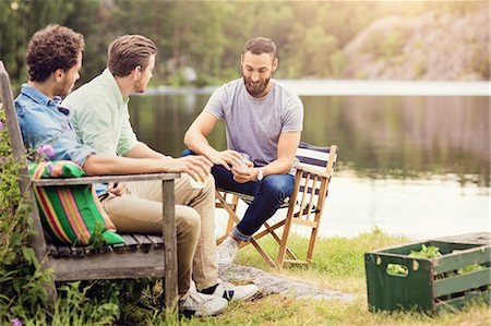Friends having drink while sitting on bench at lakeshore Stock Photo - Premium Royalty-Free, Code: 698-08886158