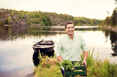Smiling man carrying vegetables crate while standing against boat at lake Stock Photo - Premium Royalty-Free, Code: 698-08886152