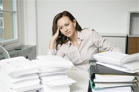 Troubled woman behind piles of envelopes Stock Photo - Premium Royalty-Free, Code: 698-03656698