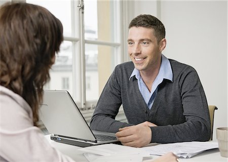Two people talking at desk Stock Photo - Premium Royalty-Free, Code: 698-03656708