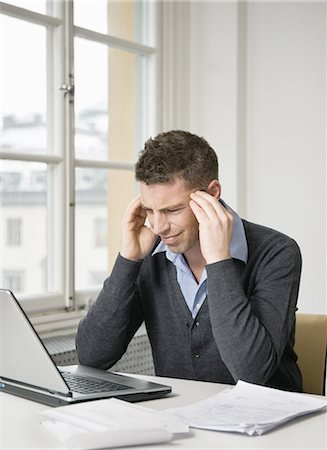 Troubled businessman using laptop Stock Photo - Premium Royalty-Free, Code: 698-03656703