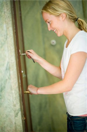 Woman unlocking the door Stock Photo - Premium Royalty-Free, Code: 698-03657514