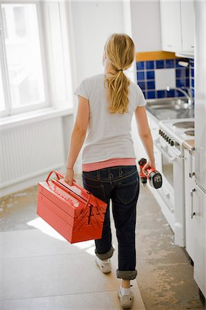 Woman with toolbox and screwdriver from behind Stock Photo - Premium Royalty-Free, Code: 698-03657523