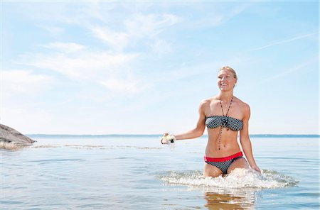 Woman walking in the water Stock Photo - Premium Royalty-Free, Code: 698-03658103