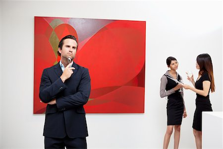 exhibition - Young man thinking with two women talking in background in art gallery Stock Photo - Premium Royalty-Free, Code: 693-05552746