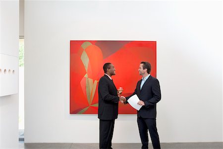 exhibition - Two people shaking hands in front of wall painting Stock Photo - Premium Royalty-Free, Code: 693-05552754