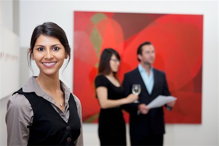 exhibition - Portrait of smiling young woman in front of a couple in art gallery Stock Photo - Premium Royalty-Free, Code: 693-05552750
