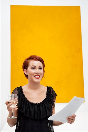 exhibition - Smiling young woman in front of yellow wall painting Stock Photo - Premium Royalty-Free, Code: 693-05552763