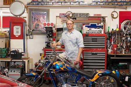 Senior man standing behind motorcycle in automobile repair shop Stock Photo - Premium Royalty-Free, Code: 693-05553160