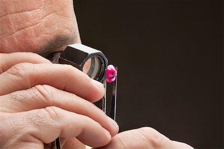 Cropped image of jeweler examining jewel over black background Stock Photo - Premium Royalty-Free, Code: 693-05553380