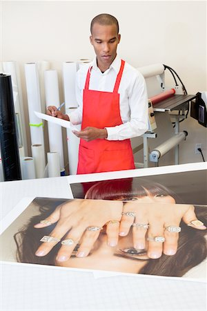 print - Man working at printing press with photo printouts on table Stock Photo - Premium Royalty-Free, Code: 693-05794021