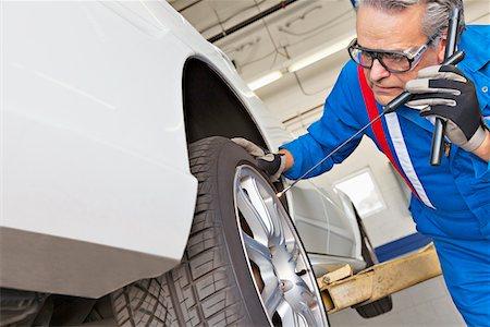 Elderly man working on car tire Stock Photo - Premium Royalty-Free, Code: 693-05794034