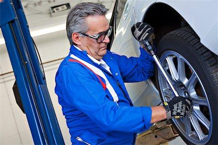 Car mechanic working on car tire Stock Photo - Premium Royalty-Free, Code: 693-05794035