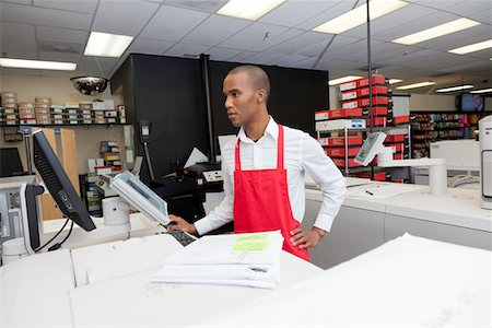 Manual worker looking at cash register machine Stock Photo - Premium Royalty-Free, Code: 693-05794030