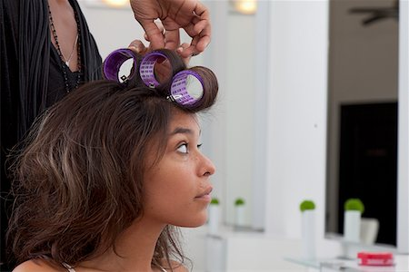 Young woman having hair curled in beauty salon Stock Photo - Premium Royalty-Free, Code: 693-05794097