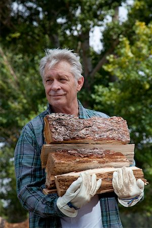 forestry - Senior man carrying firewood Stock Photo - Premium Royalty-Free, Code: 693-05794384