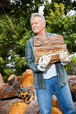 Senior man carrying firewood logs Stock Photo - Premium Royalty-Free, Code: 693-05794385