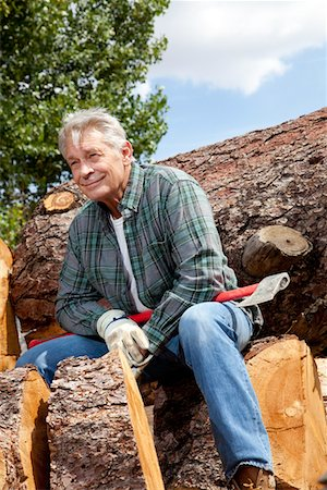 Senior man sitting on wood logs with an axe Stock Photo - Premium Royalty-Free, Code: 693-05794388