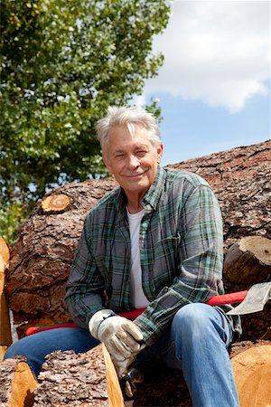 forestry - Portrait of smiling senior man sitting on logs Stock Photo - Premium Royalty-Free, Code: 693-05794389