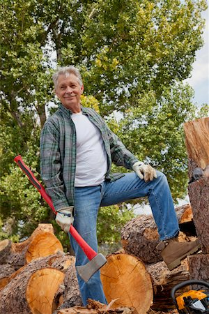 forestry - Lumberjack with an axe standing with stack of chopped firewood in background Stock Photo - Premium Royalty-Free, Code: 693-05794383