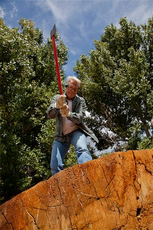 forestry - Low angle view of man about to chop wood Stock Photo - Premium Royalty-Free, Code: 693-05794395