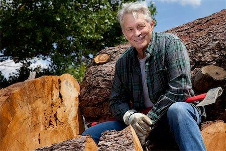 forestry - Smiling senior man sitting on logs Stock Photo - Premium Royalty-Free, Code: 693-05794390