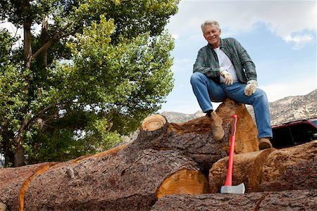 forestry - Low angle view of man sitting on a huge tree trunk Stock Photo - Premium Royalty-Free, Code: 693-05794393