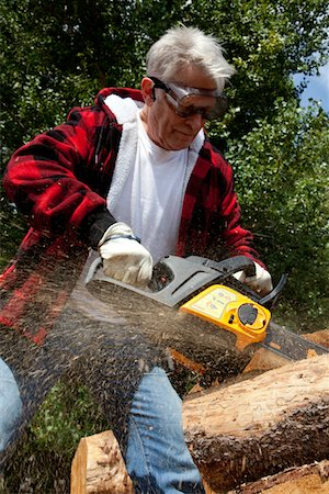 forestry - Forestry worker cutting tree with chainsaw Stock Photo - Premium Royalty-Free, Code: 693-05794404