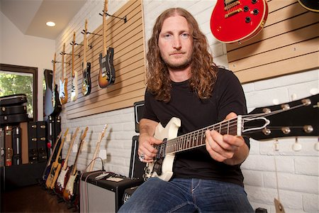 sale - Portrait of serious mid adult man sitting in guitar store Stock Photo - Premium Royalty-Free, Code: 693-05794451