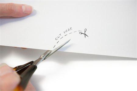 Hand using scissors to cut paper Stock Photo - Premium Royalty-Free, Code: 693-05794500