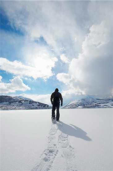 Man walking in snowshoes through snow, back view Stock Photo - Premium Royalty-Free, Image code: 693-06018060
