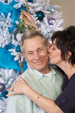 Senior woman kissing man under mistletoe Stock Photo - Premium Royalty-Free, Code: 693-06019508