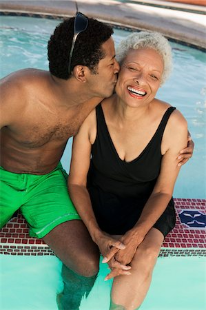 seniors woman in swimsuit - Man sitting on edge of swimming pool, kissing mother on cheek, elevated view. Stock Photo - Premium Royalty-Free, Code: 693-06013573
