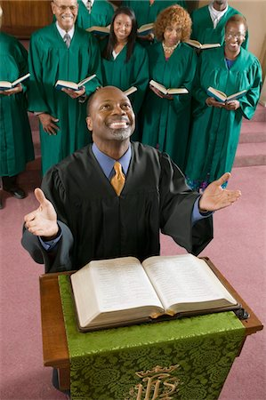 Happy preacher with Bible at church altar looking up, high angle view Stock Photo - Premium Royalty-Free, Code: 693-06013976