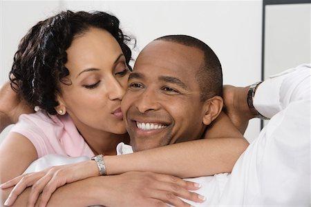 Woman Kissing Smiling Man Stock Photo - Premium Royalty-Free, Code: 693-06020067