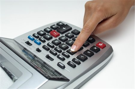 Woman using calculator, close-up of finger Stock Photo - Premium Royalty-Free, Code: 693-06020363